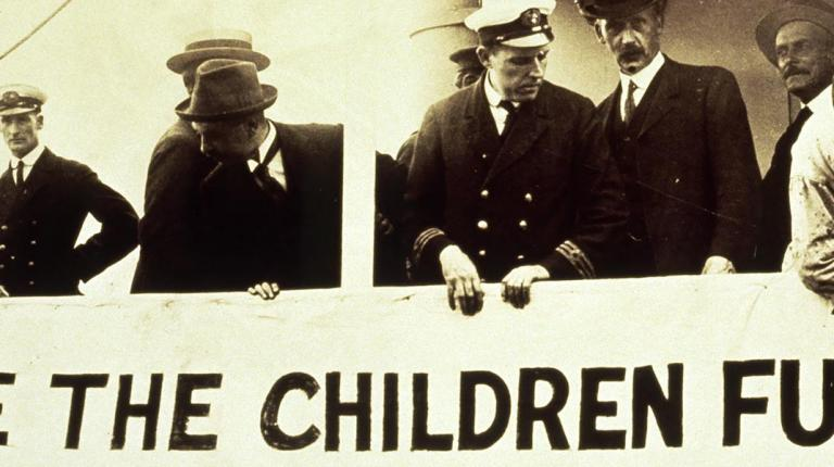 sailors standing behind save the children banner